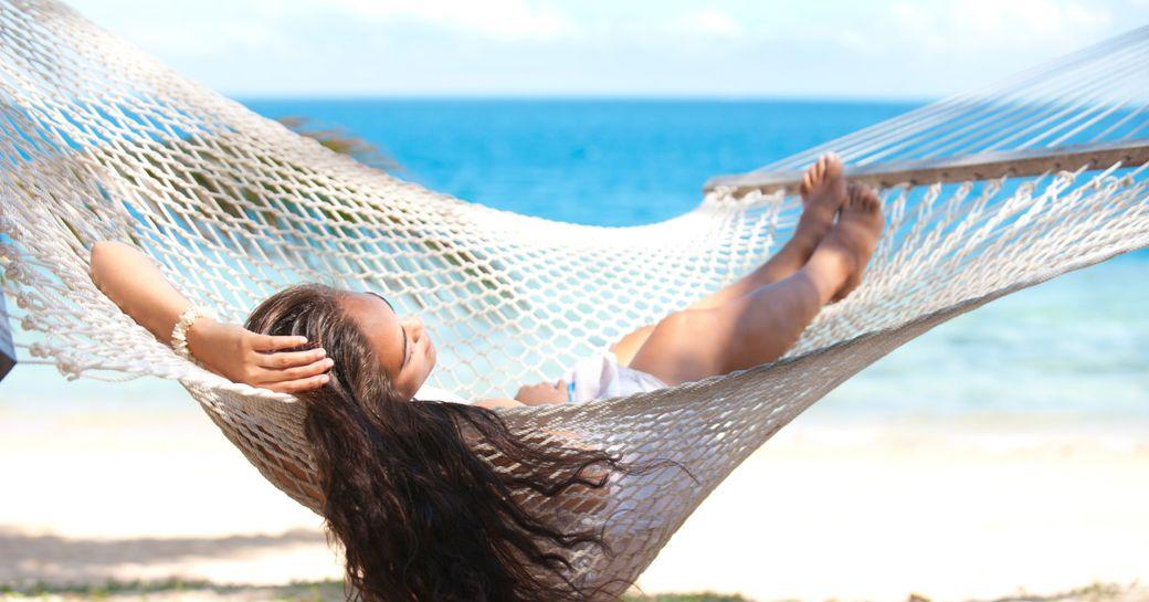 charter guest relaxes in a hammock on a Fijian beach
