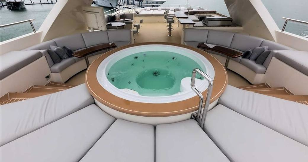 spa pool surrounded by sunpads and cocktail tables on the sundeck of expedition yacht SAFIRA