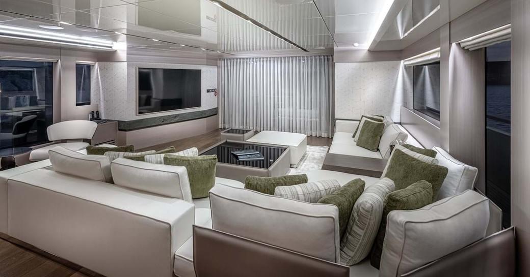 Main saloon area with comfortable sofas facing large TV on explorer yacht 'Seven Diamonds'