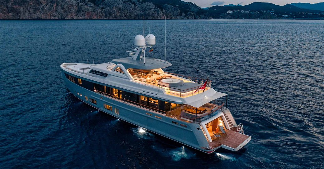 aft view of motor yacht CALYPSO as deck spaces light up for dusk