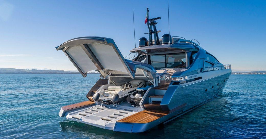 Tender garage of motor yacht BEYOND revealing tenders. Yacht is on calm sea.