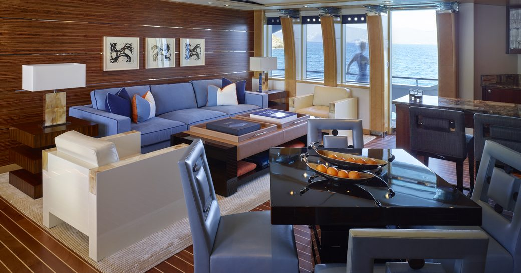 Bright main salon on Victoria Del Mar, with colorful sofas and wooden panelled floor and walls, and doors onto deckside patio