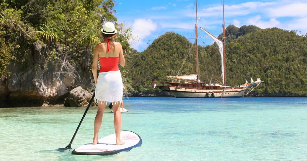 charter guest tries at a paddle board as luxury yacht LAMIMA anchors nearby