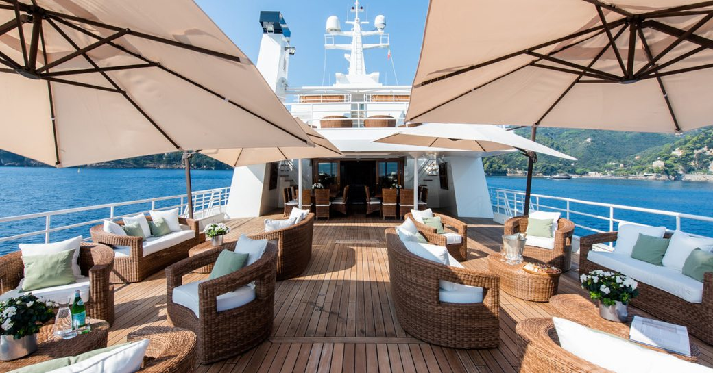 Seating and tables on deck of superyacht Bleu De Nimes