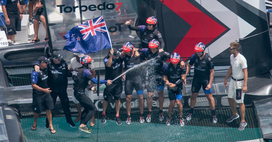Emirates Team New Zealand celebrate on board foiling catamaran after racing to victory in the 35th America's Cup