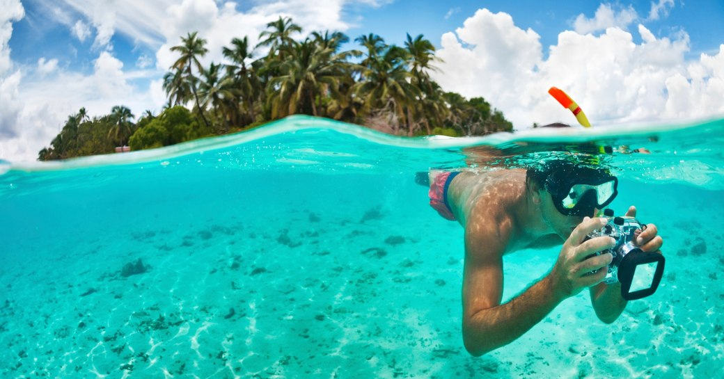 A snorkeler takes photos while swimming in the beautiful waters of the Maldives