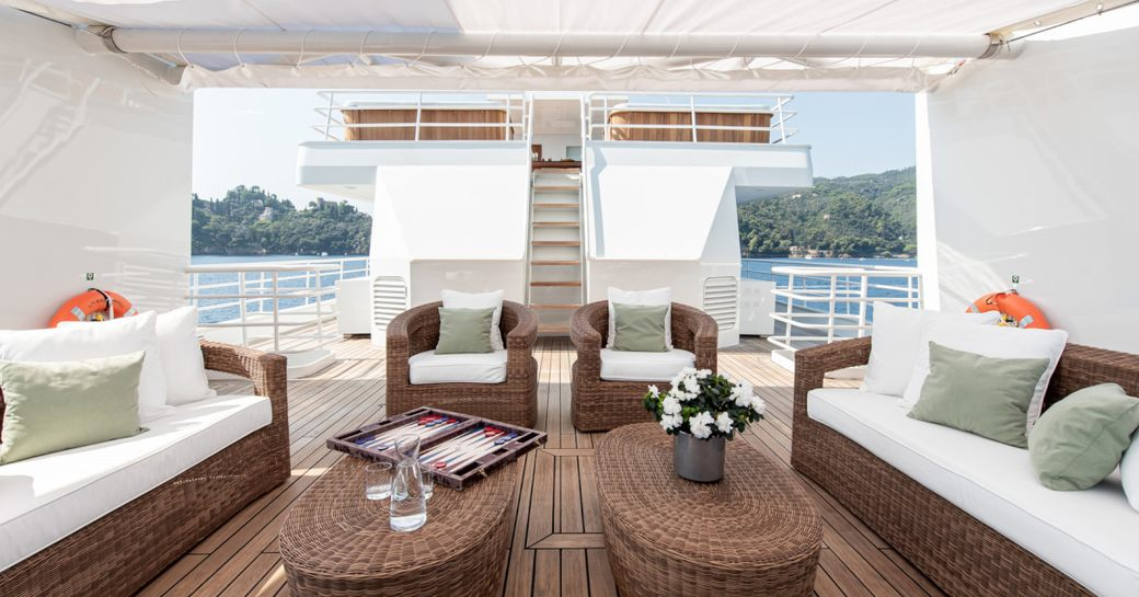 Lightly covered seating and rattan tables on superyacht Bleu De Nimes
