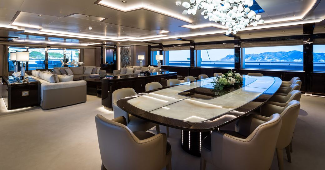 Open plan interiors on superyacht O'PARI with dining table and comfortable chairs and large windows