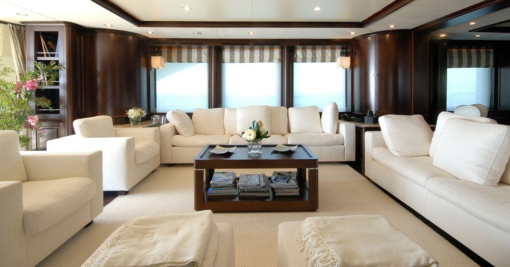 elegant main salon lounge with dark woods and light upholstery on board superyacht 'Elena Nueve'