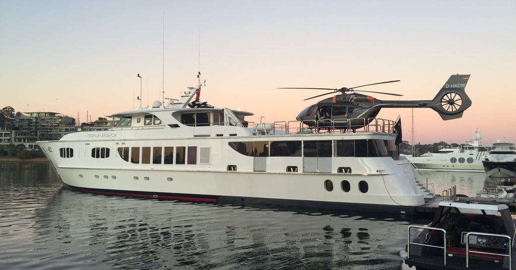 helicopter lands on expedition yacht on Caroline as the sun sets