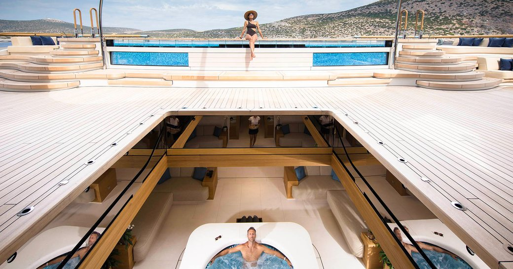 the main aft deck and beach club of superyacht FLYING FOX by lurssen which features a large glass encased pool and boasts a retractable deck that opens yup to the jacuzzi in the beach club