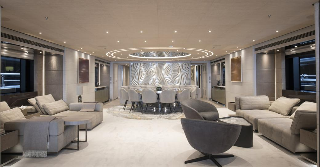 Lightly colored living area on superyacht SEVERIN'S with number of comfortable chairs and sofa, and circular dining table at far end