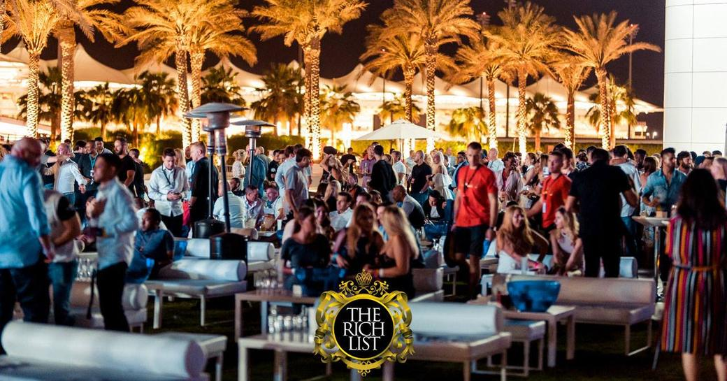People sitting outside at The Rich List at Palm Island event at Yas Viceroy Hotel with palm trees lit up in background