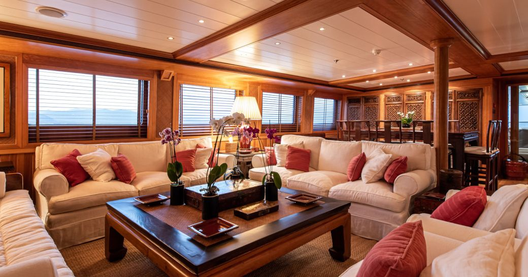 Ornate social area on superyacht 'Bleu De Nimes' with cream sofas and wooden detailing
