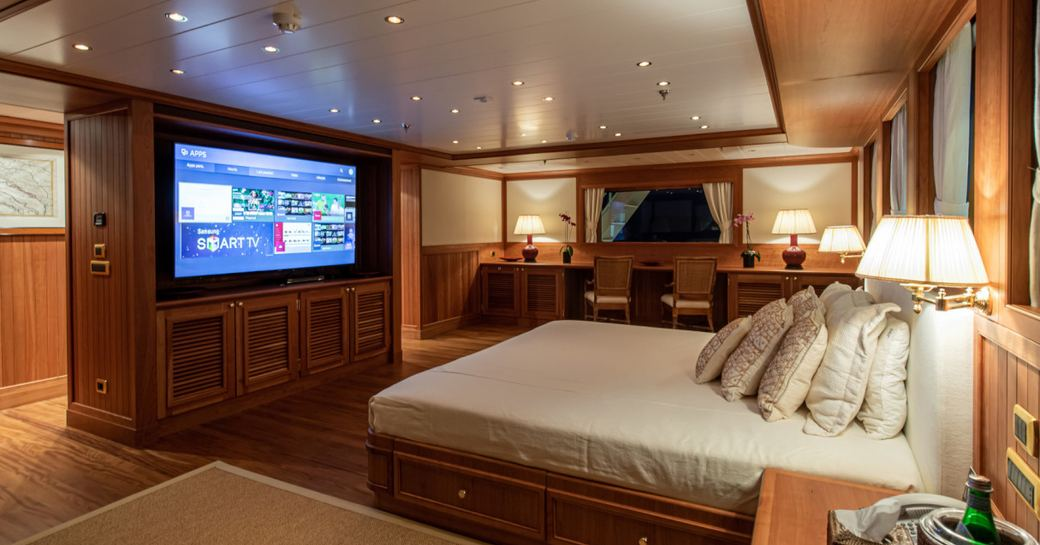 Large master suite on superyacht 'Bleu De Nimes' with bed facing flat screen TV in wooden detailed room