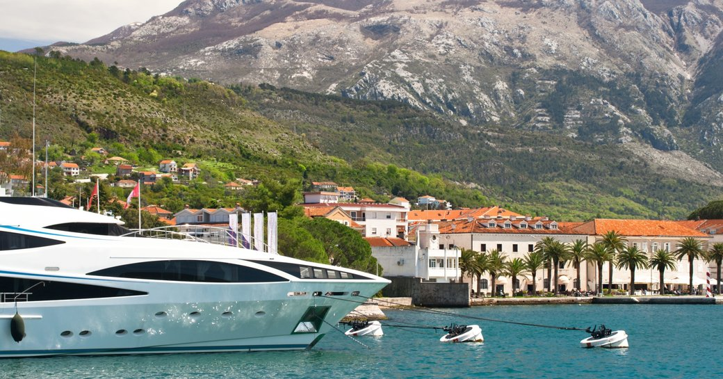 superyacht lines up in yacht club in Montenegro looked over by dramatic mountain range