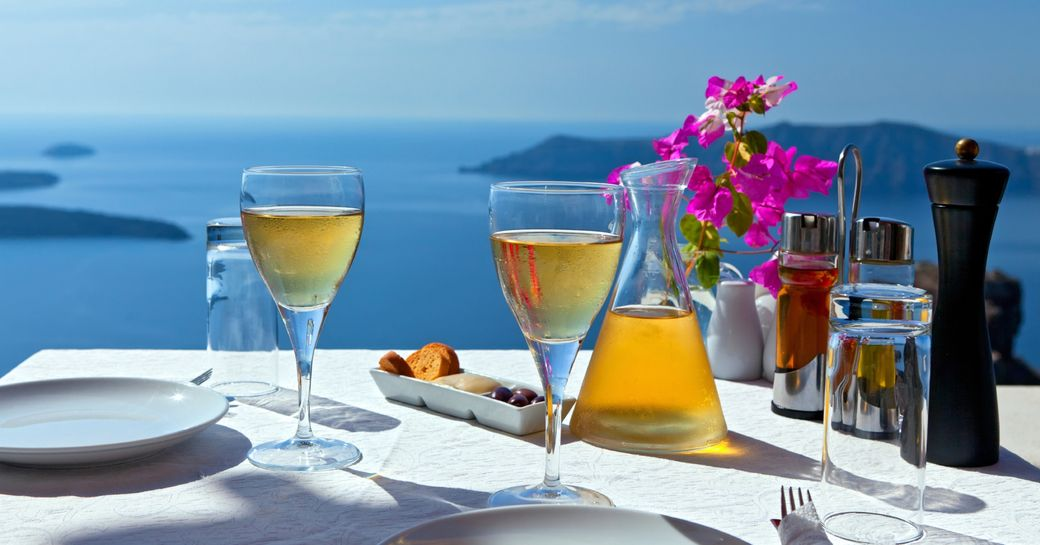 table set with local wine in Oia with stunning views of the Santorini coast in Greece