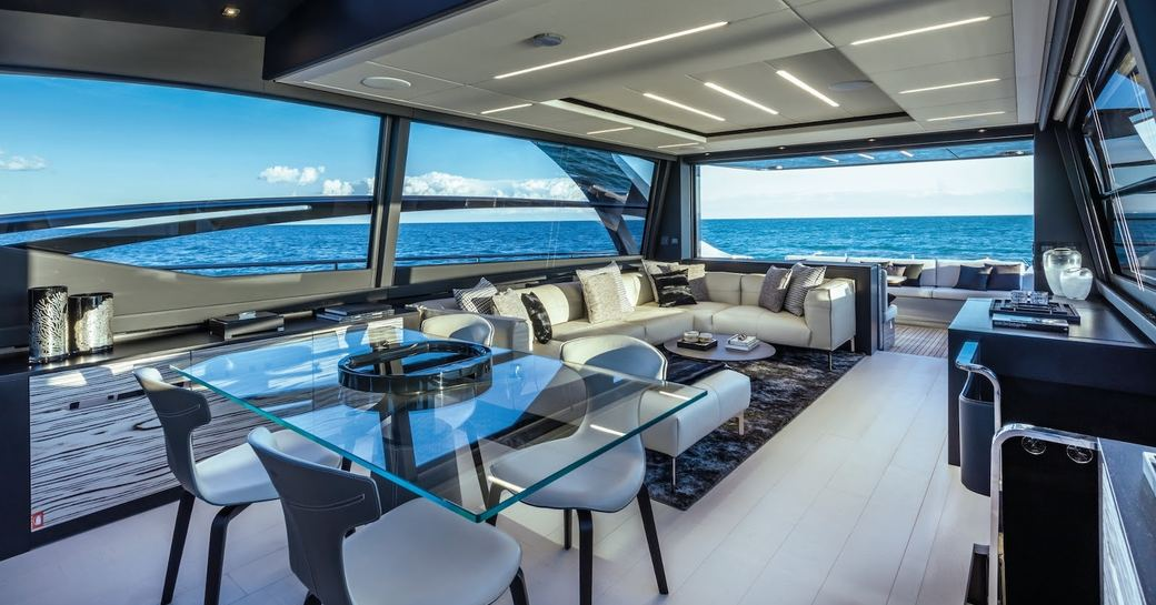 Dining area under cover on motor yacht BEYOND, with tables and chairs and comfortable sofa and sea visible in background.