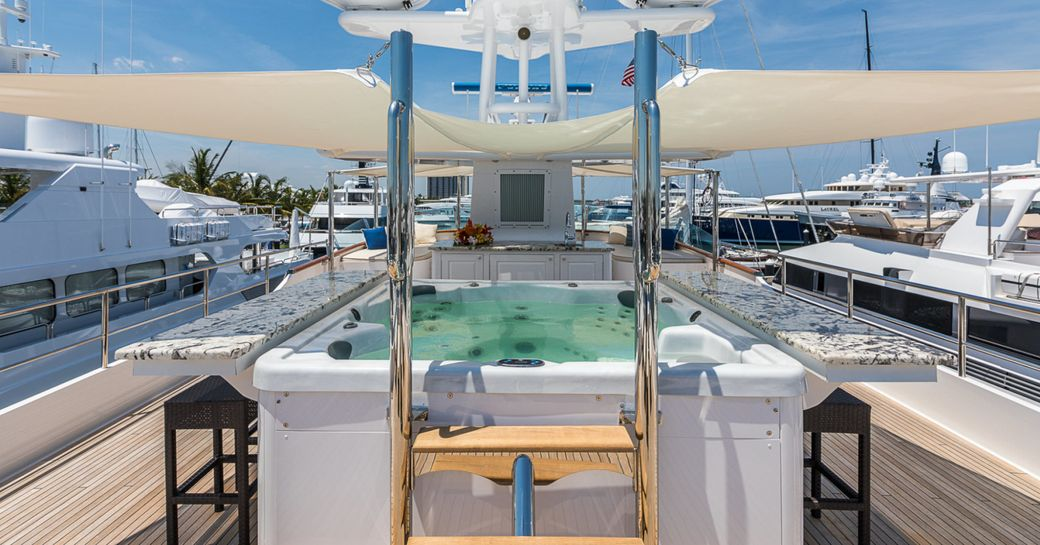 Jacuzzi surrounded by bar on sundeck of superyacht PRAXIS