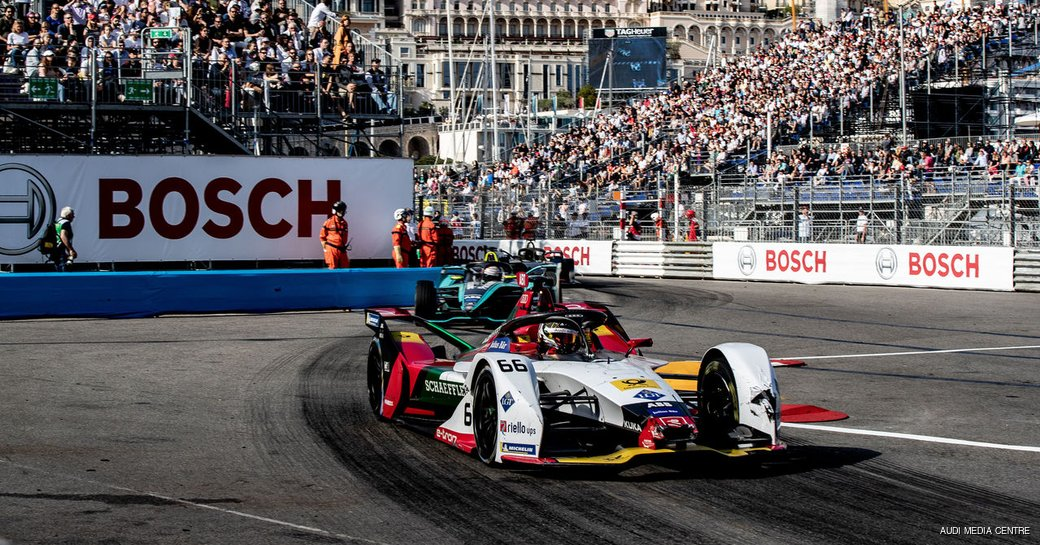Formula E race in progress, racer in foreground with stands and spectators in background.
