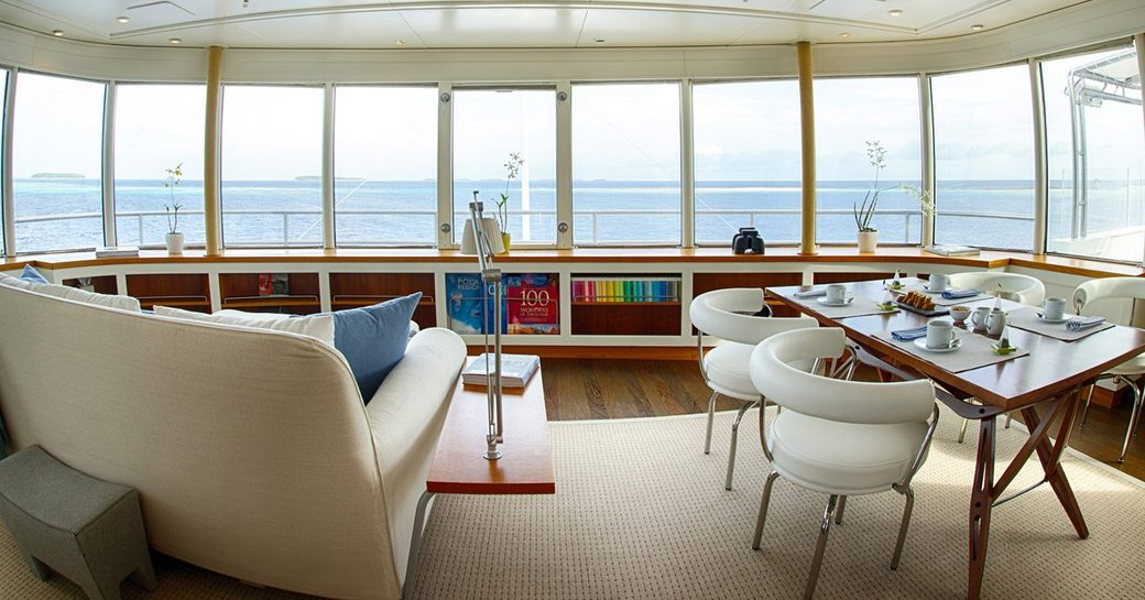 sofa and table and chairs with large windows on board superyacht SENSES