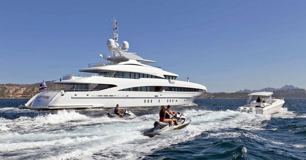 motor yacht Inception underway alongside jetskis on a Caribbean yacht charter