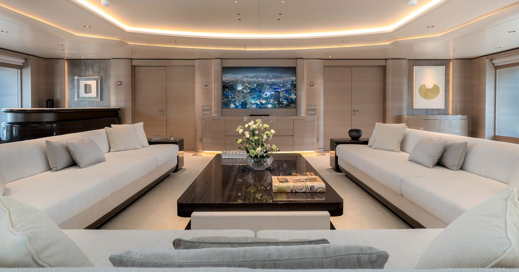 Lightly colored sofas surround wooden dining table on superyacht O'PARI