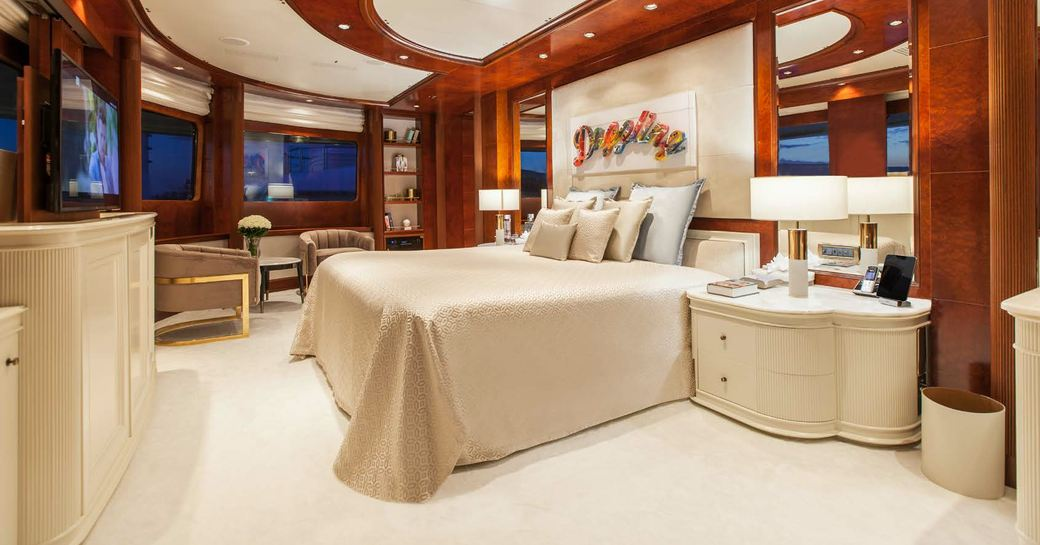 Double bed in Cabin on O'MEGA superyacht with pastel colors and wooden interior