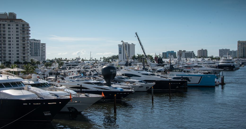 Yachts lined up at FLIBS2019 with high rise buildings in background