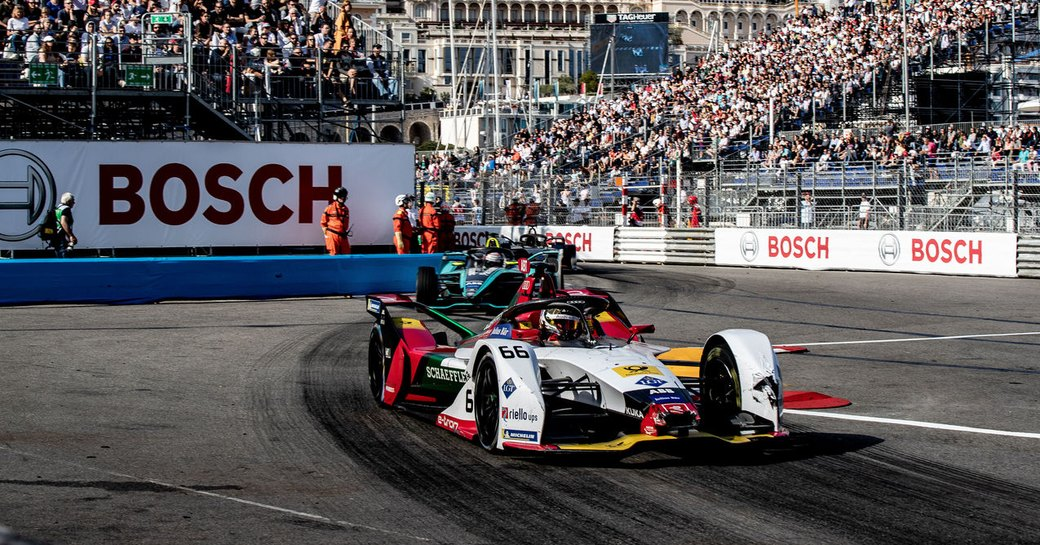 Racers taking part in Monaco E-Prix, surrounded by track and stands full of spectators.