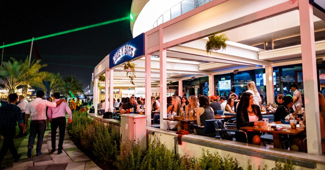 Diners at tables of outdoor terrace of Stars N Bars overlooking Yas Marina in Abu Dhabi