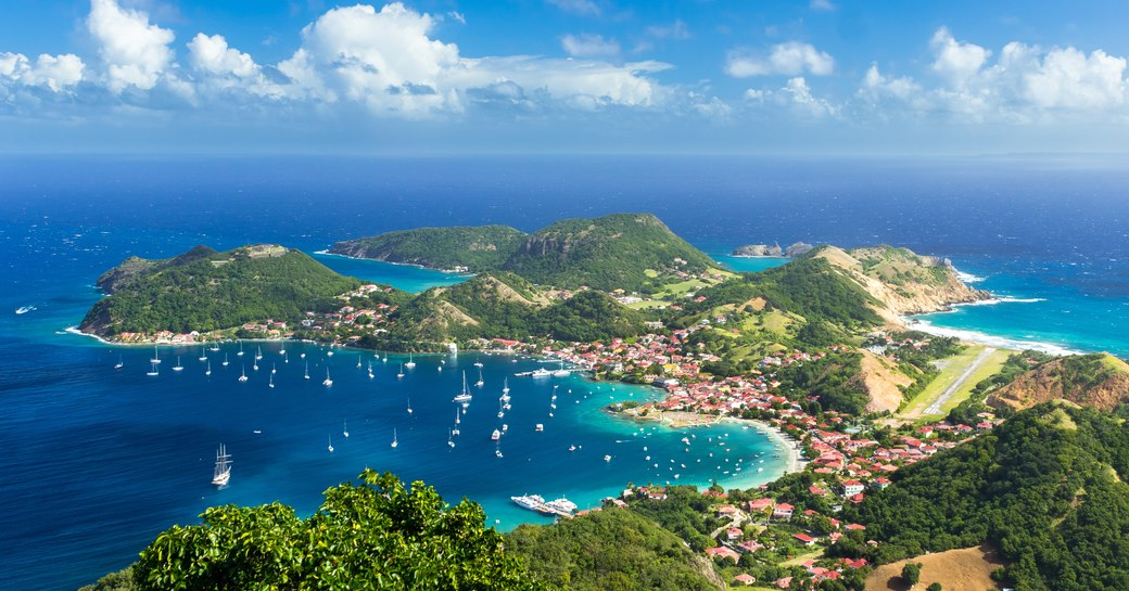 Island Town with hilly, green interior and lots of yachts on the water in Guadeloupe