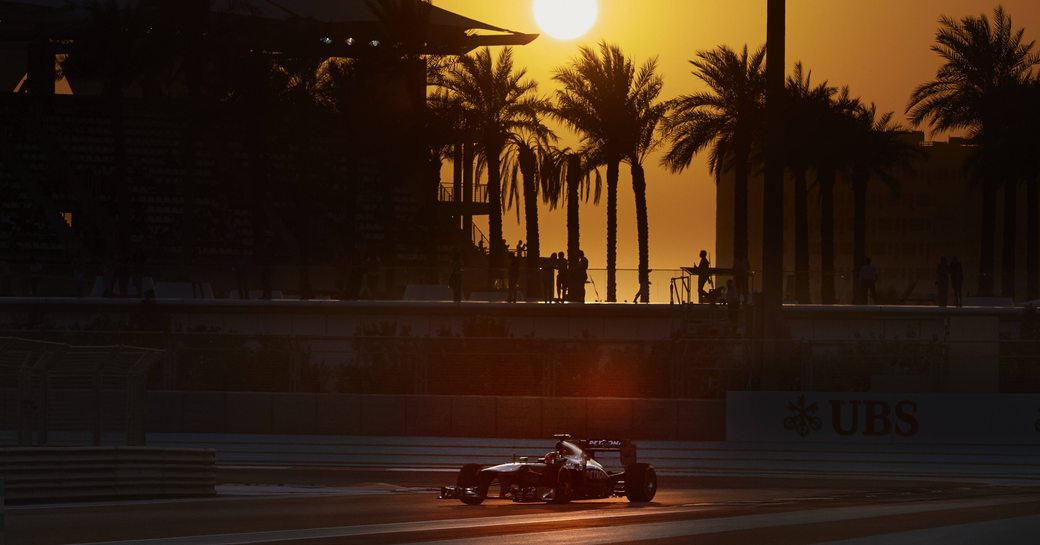 Racer on Abu Dhabi Grand Prix track at sunset, sun setting on background casting shadows over track.