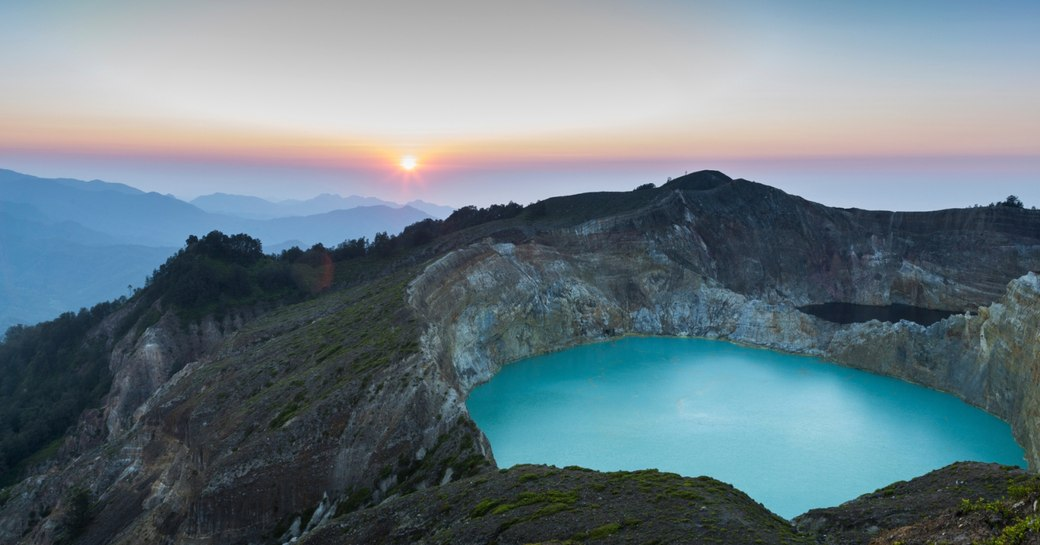 A crater lake of Mount Kelimutu as the sun sets