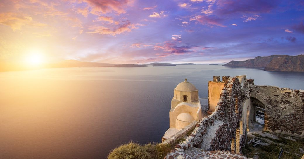 shot of the sun setting from Oia in Santorini with views across the caldera