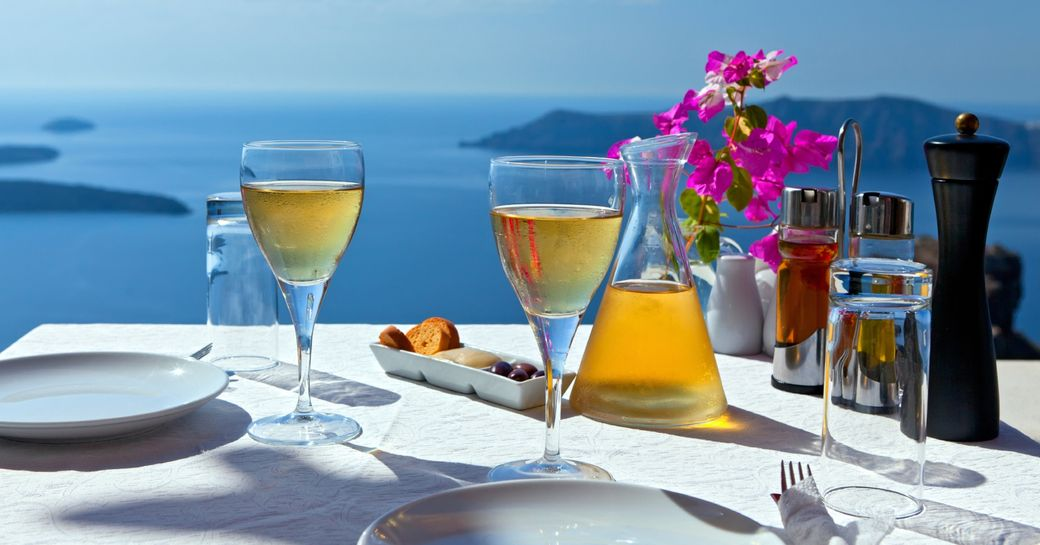 table set for two in cliff-side restaurant in Mykonos, Greece
