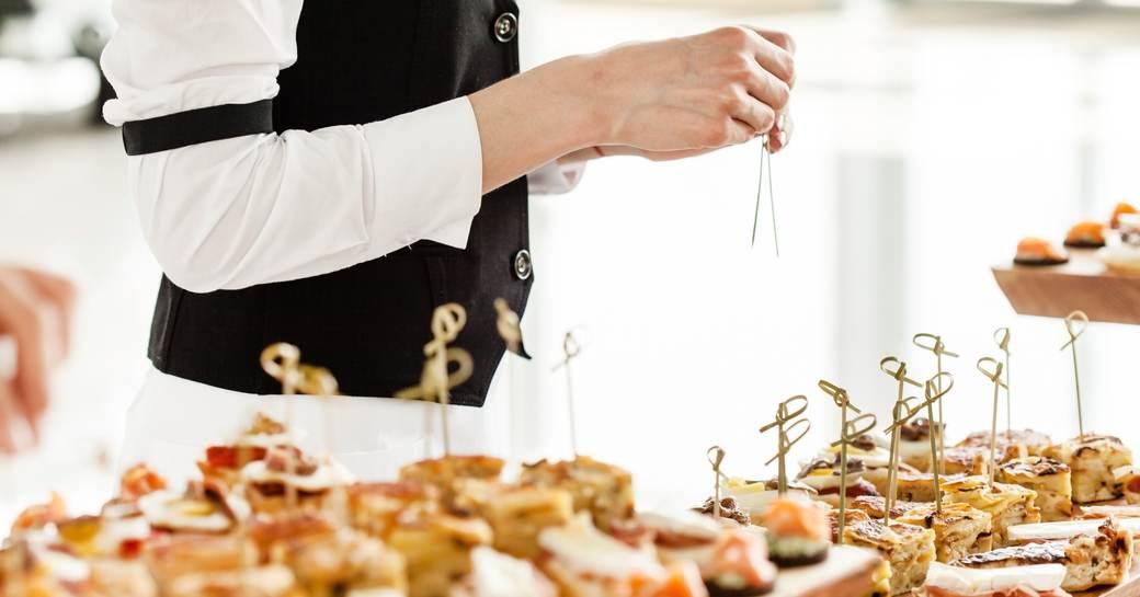 waiting staff in black waistcoats and white shirts prepare gourmet buffet