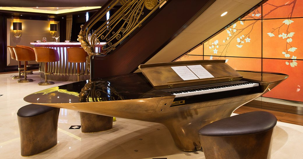 piano built into a bar with video walls and staircase behind on board superyacht KISMET
