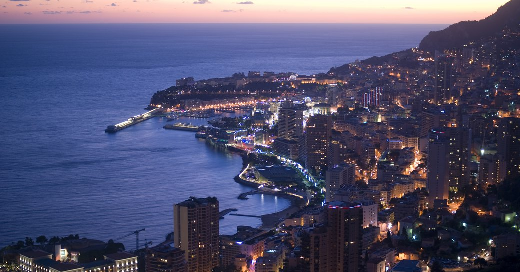 View across Monaco coastline at night with many buildings lights visible