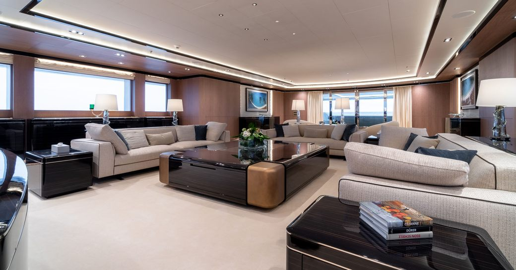 large cream sofas surround a wooden coffee table in the main salon aboard superyacht O'PTASIA