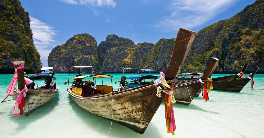 traditional fishing boats on the shore of a white-sand beach in Phuket