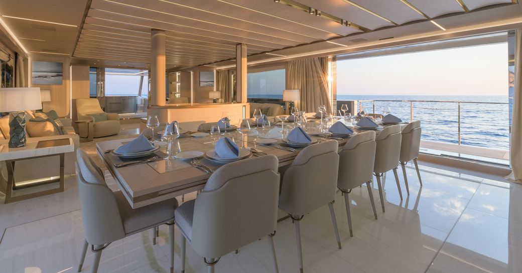 Formal dining table laid out with balcony open and view to sea on superyacht EIV