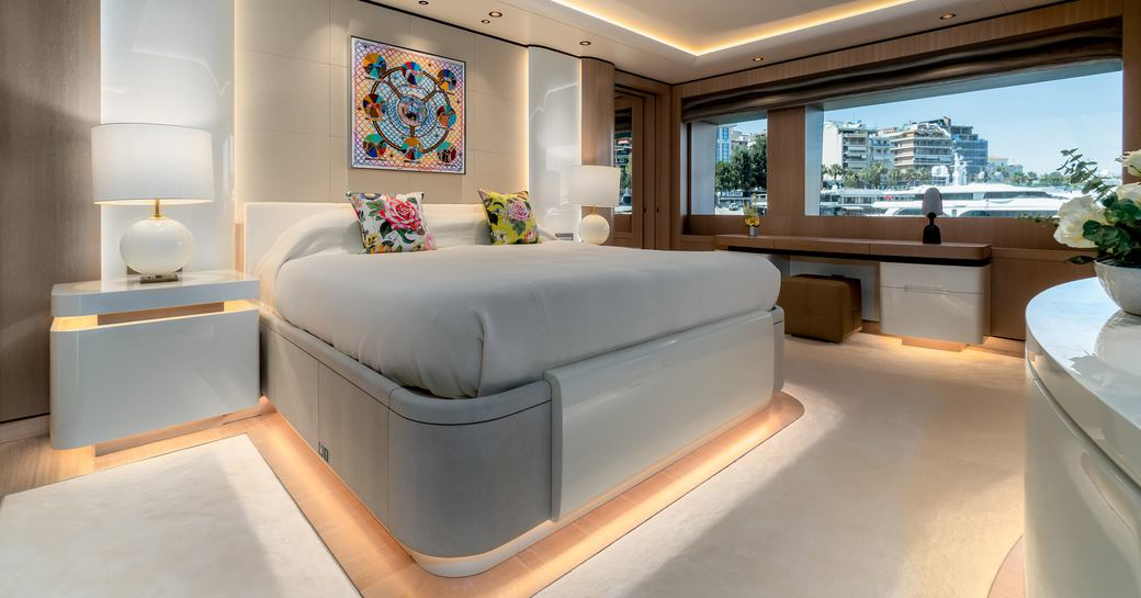 Large stateroom on superyacht O'PARI, with buildings visible through window to the right hand side