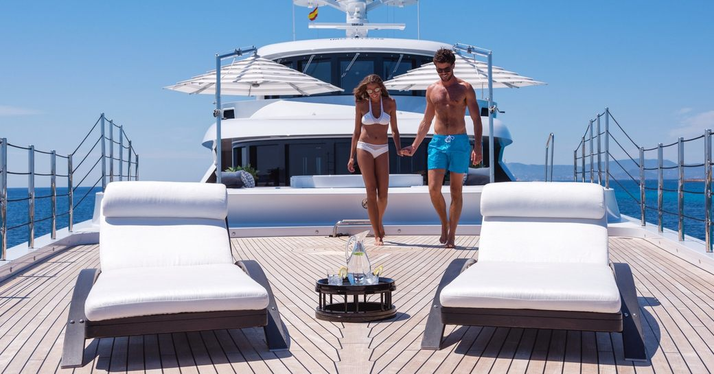 charter guests head to the sun loungers on the owner's deck of superyacht 11/11