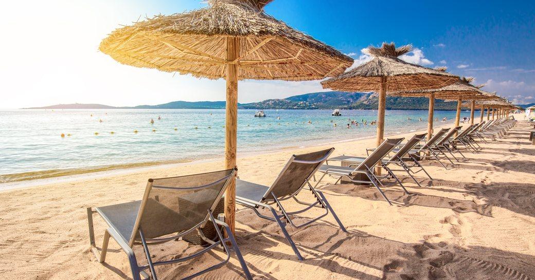 sun loungers line up on San Ciprianu beach in corsica