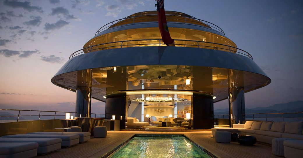 Outdoor area on superyacht SAVANNAH lit up at night with pool visible