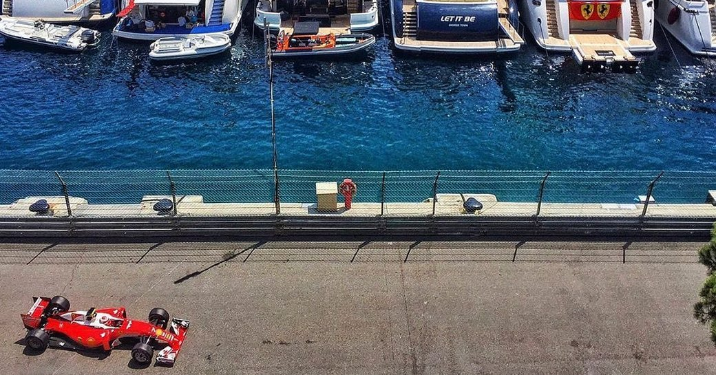 Aerial image of car on the race circuit opposite a fleet of charter yachts during the Monaco Grand Prix