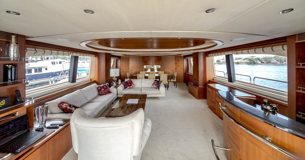 warm woods and neutral furnishings of the main salon aboard luxury yacht Antonia II