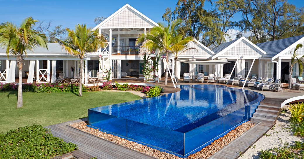 thanda island villa accommodation with infinity pool with glass rim in foreground and suites in background, with palm trees lined up infront