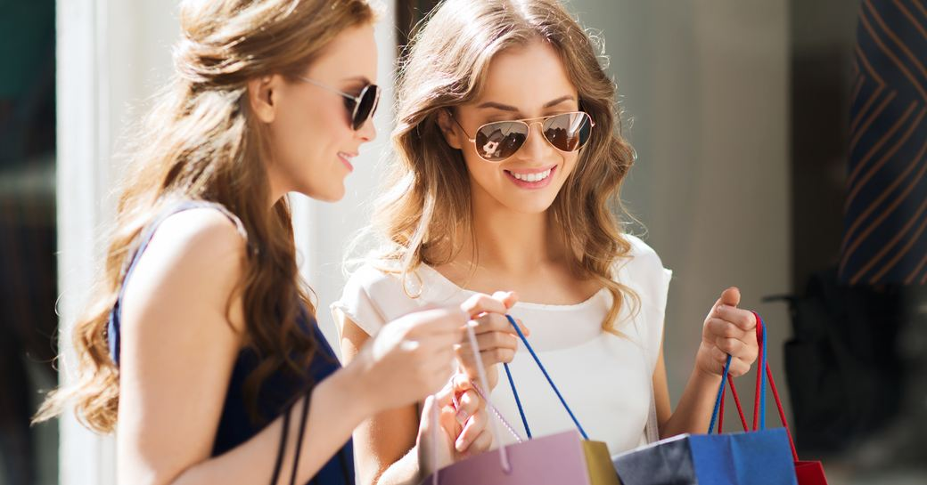 women in the sunshine carrying designer shopping bags in monaco